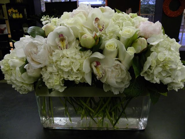 All White, Long And Low Centerpiece Containing Peonies, Hydrangea, Orchids, Roses, And Tulips