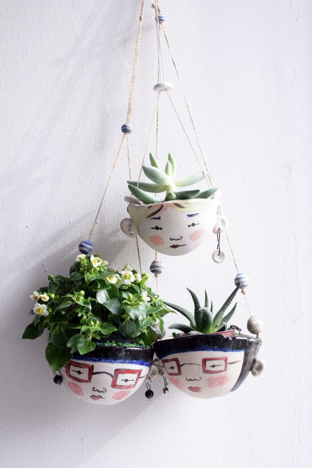 Ceramic hanging planterAstrid hipstergarden plant pot is part of Green Home Accessories Hanging Planters - OVER THE UPCOMING CHRISTMAS PERIOD I WILL BE HAVING A BREAK FROM THE STUDIO SO PLEASE ALLOW TWO WEEKS FOR MANUFACTURE! A hand formed stoneware planter with hand painted character  Quirky, rustic and wobbly  Meet Astrid  Suitable for very small succulents  I would recommend a sprinkle of fine gravel in the bottom to allow for drainage  (Can also be made with a drainage hole for outdoor usejust get in touch!) Has little earrings and handmade ceramic bead decoration  Hung on a length of cotton cord string  Lips and glasses frames have transparent glaze on them for a glossy look  Could also hang in the kitchen to hold garlic bulbs, or could grow cress  Approx bowl dimensions, 11cm across top, 7 cm at deepest point, string hangs at approx 42 cm length   Standard delivery but get in touch if you want trackable  The planter sent may vary slightly from the one in the image due to the handmadeness of the product  Plant not included!!