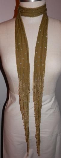 This offer is for a beautiful olive green double layer scarf edged with clear Aurora Boreales olive green heart seed beads and stitched sequence throughout and a profussion of fringes of the same beads on both ends. This a perfect accent for day w... $24.95