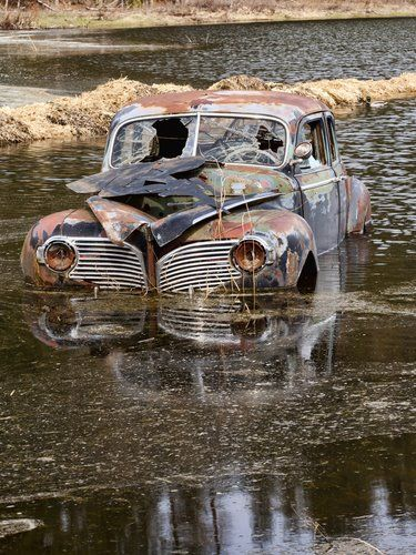 An Old Antique Car Sits Swamped In A Flooded Pond Whoever Left