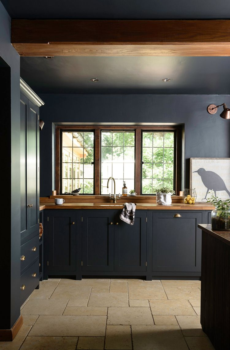 Dark and moody kitchen decor with dark grey cabinets and walls lifted by iroko wood worktops and pale quarry tiled floor devols petersham kitchen