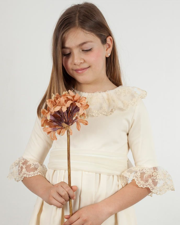 f13b4bd42 Vestido de ceremonia Rita en canutillo crema y encaje romántico en cuello y  mangas. Puedes completarlo con una flor en el lazo ¡Quedará ideal!