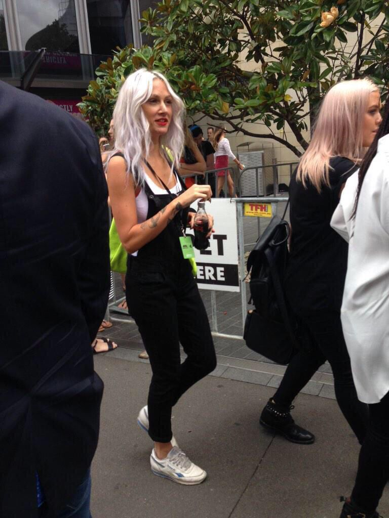 Lou Teasdale: silver platinum, red lips, white tank, black cuffed skinny overalls, sneakers.