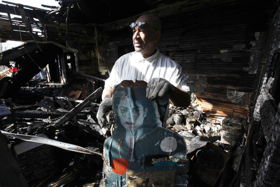SIFTING THROUGH: Tyree Guyton, creator of the Heidelberg Project outdoor art installation, found a burned Michael Jackson poster in the remains of the 'Obstruction of Justice House' in Detroit on Friday. The 'Obstruction of Justice House,' one of the project's most popular structures, was badly damaged in a fire that started early Friday morning. (Paul Sancya/Associated Press)
