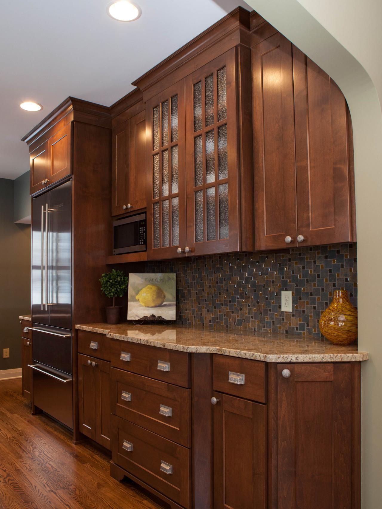 This craftsman style home was built in the 1940s and remodeled to preserve the historical character while adding modern amenities. The updated kitchen features Alder cabinetry with glass-front cabinets and an understated backsplash that brings out the warm browns in the wood. #craftsmanstylehomes
