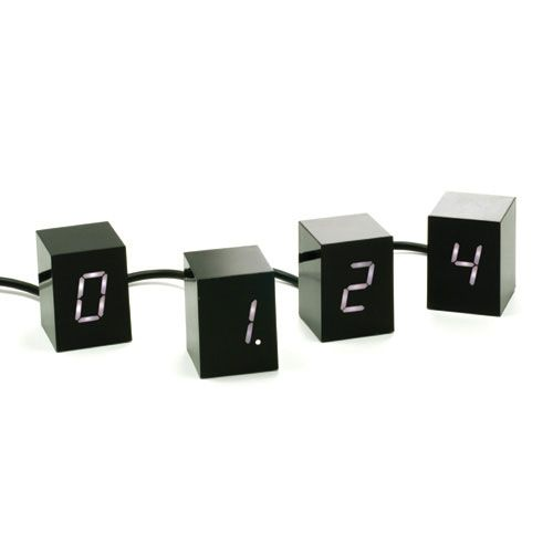 Designer Jonas Damon    Material: ABS, RoHS Compliant Electronics    Dimensions: 2 x 8 x 1.5 inches    An alarm clock consisting of four 2 inch tall cubes. Each cube displays one glowing LED digit to make up the time display. Unlike static boxes usually associated with alarm clocks, this interactive collection of changing numbers can be arranged in any configuration.
