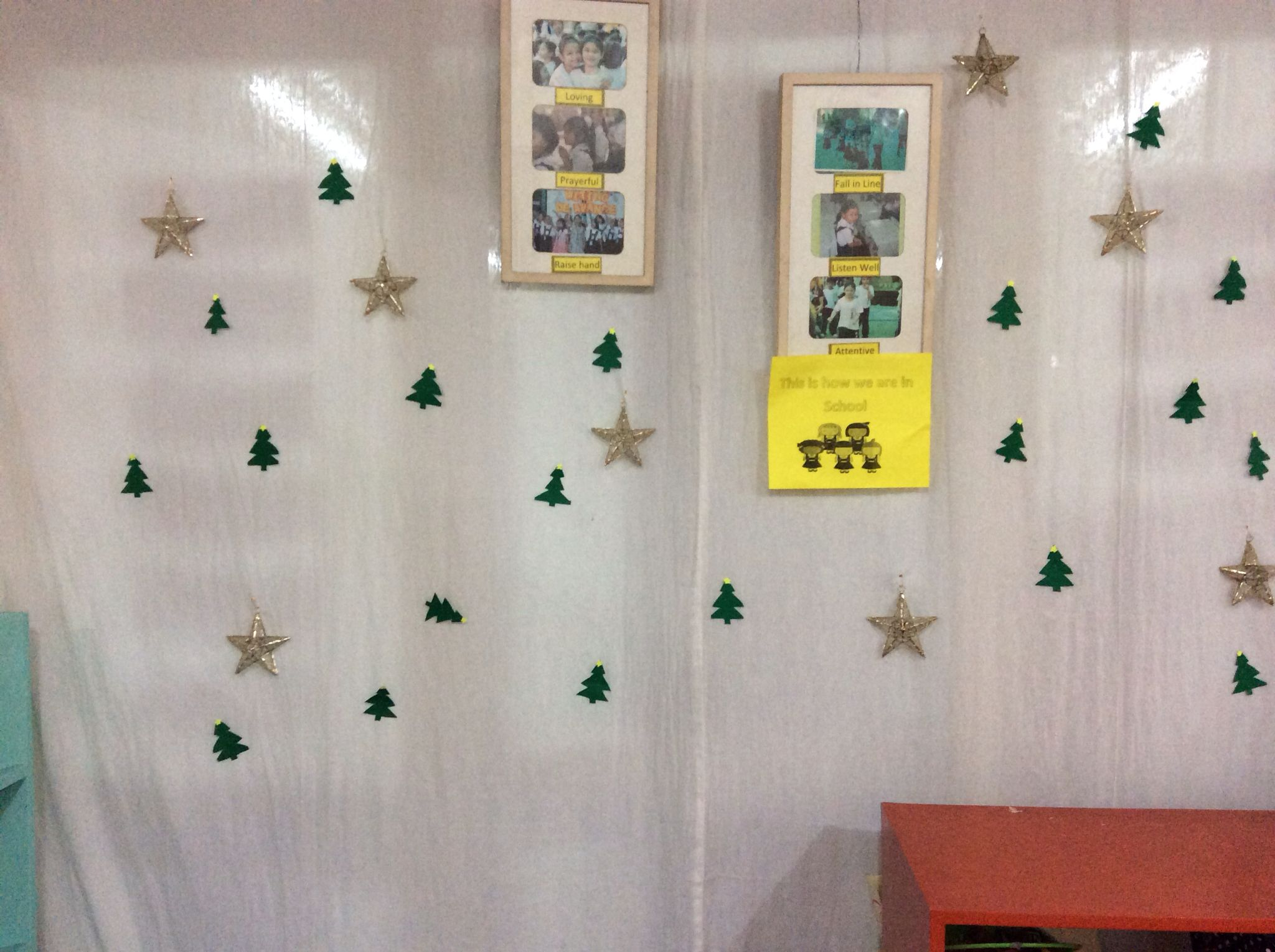 A simple christmas decoration for the classroom. Cut outs and ornaments pinned to the curtain
