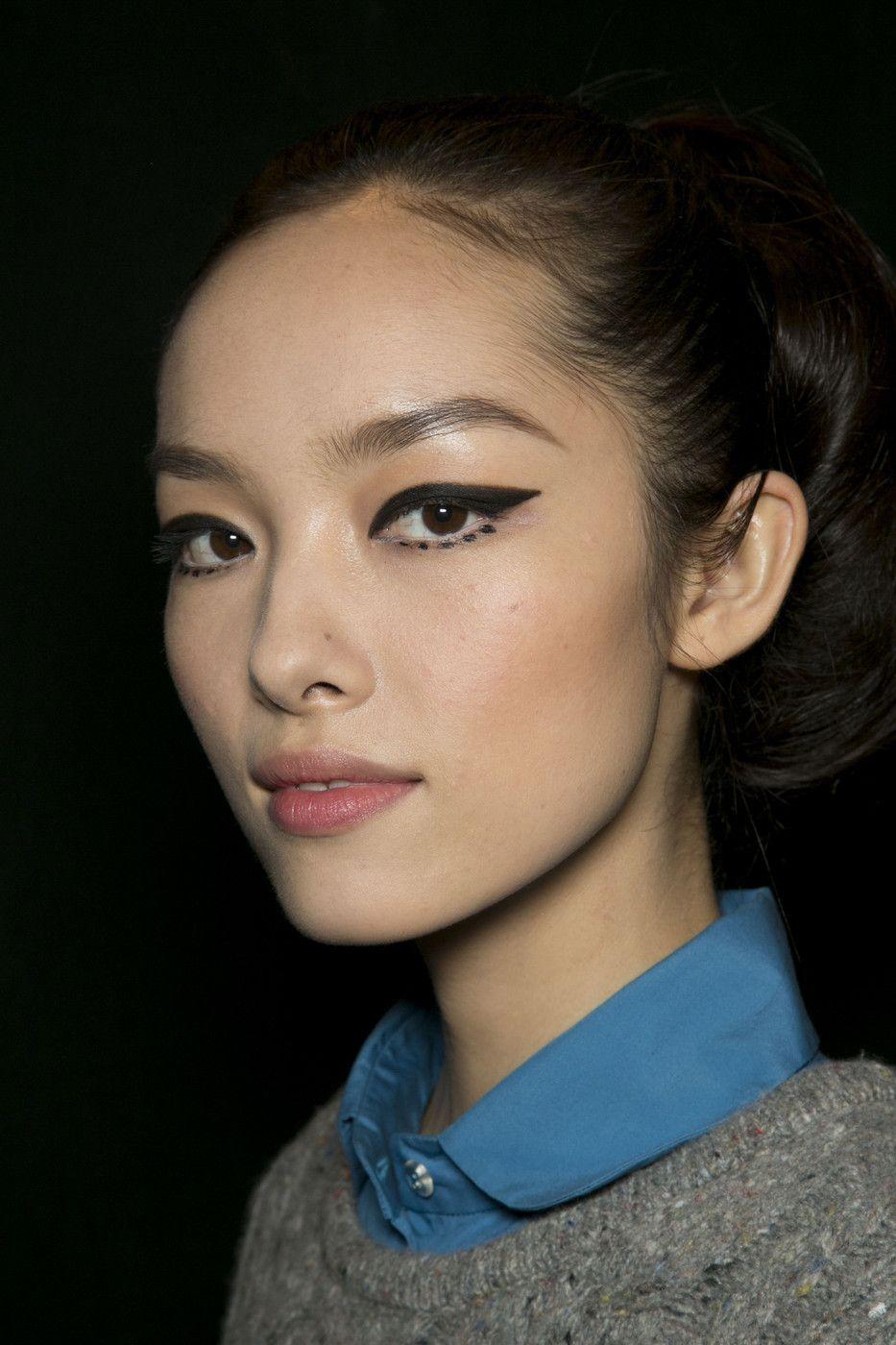 graphic winged eyeliner, collared blue shirt & grey