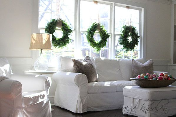 Wreath on windows//white furniture//large bowl of vintage ornaments.