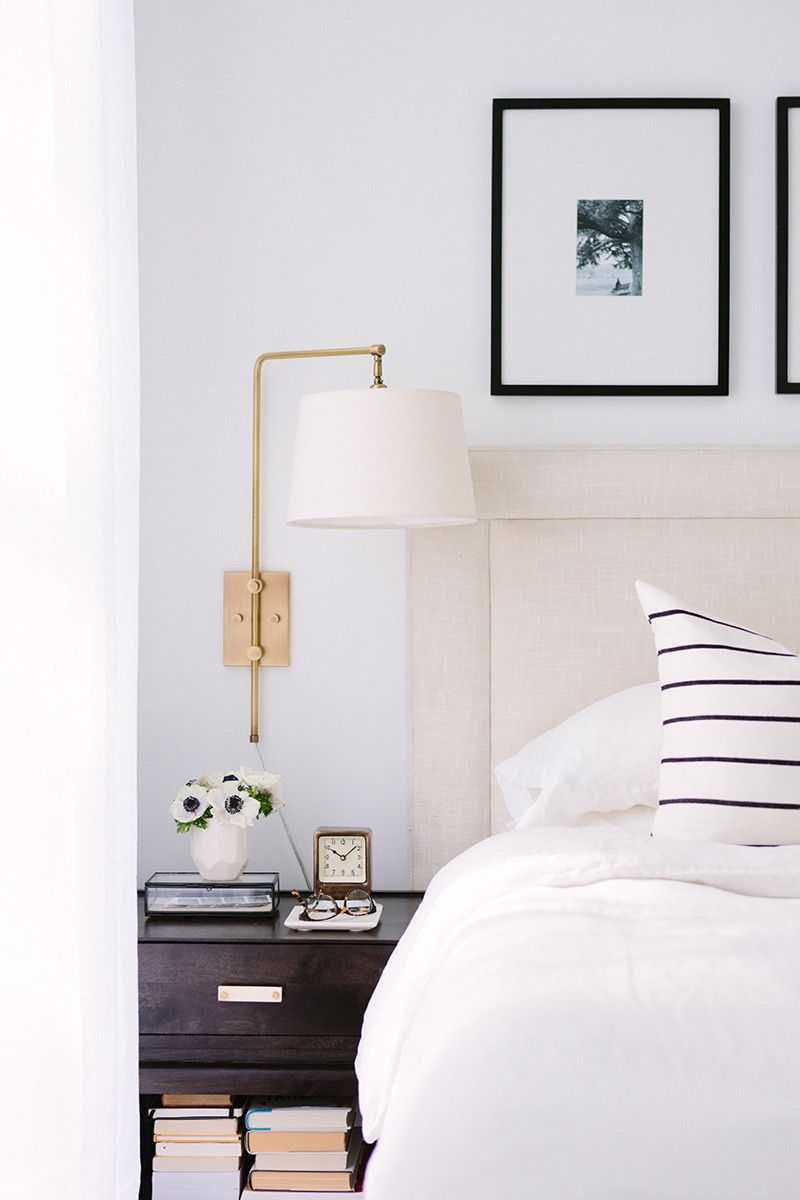 Black and white bedroom with brass swing arm lamp