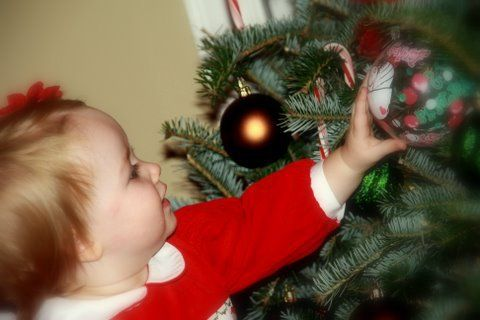 Sweet baby reaching for her first ornament