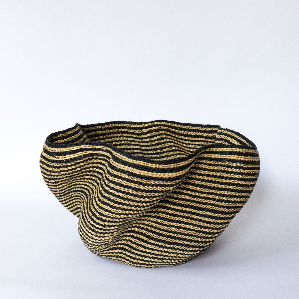 An eye-catching basket that combines organic lines, geometric patterns and natural materials resulting in a piece that's simultaneously understated and elegant. Use it as chic storage for throw blanke