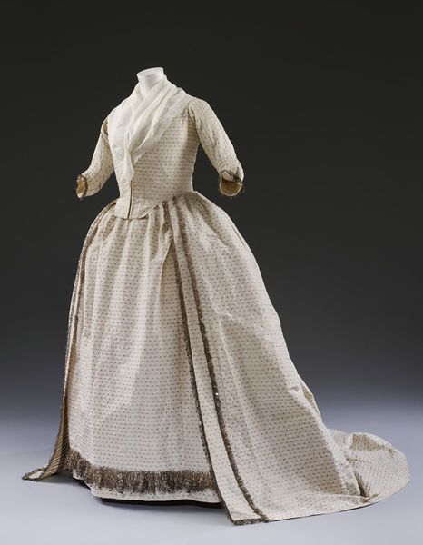 Wedding dress, Great Britain, 1779. This robe and petticoat is made of white silk woven with silver strip in a design of small silver leaves. It is decorated with a fringe made of strands of silver thread, strip and spangles, interspersed with tassels of the same materials. White and silver became popular colours for brides after Oliver Goldsmith's play, The Good-Natur'd Man was first performed in 1768. V&A