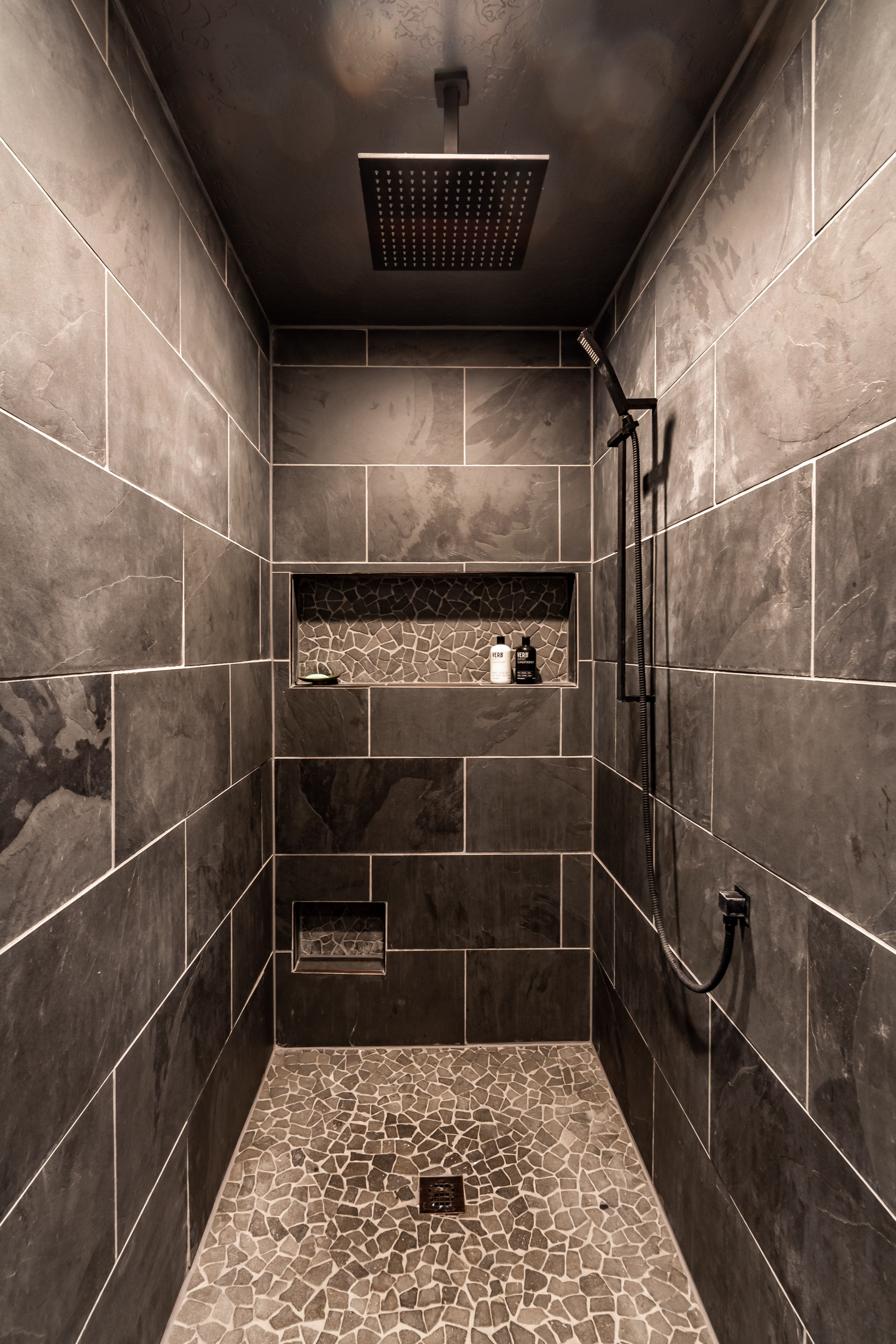 Cave like relaxation dark shower tile rain shower head