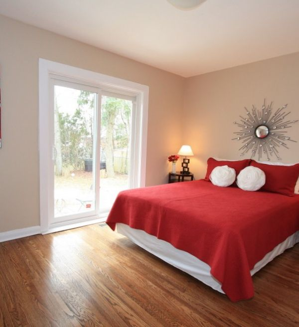 Calm Red Bedroom Interior With Wooden Floor And White Wall Paint Color Mounted Round Shaped Mirror Also Cute Cushions Cool Bedside Table