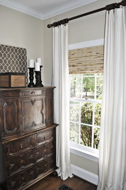 Woven Roman Shades Layered Under Ivory Drapes Mounted High