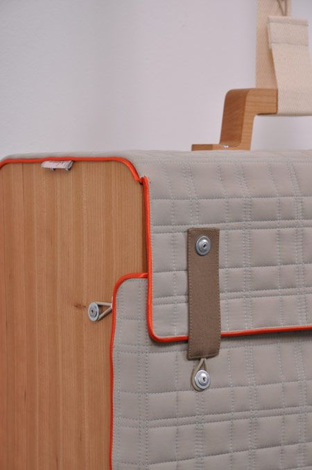 Suited Case by Erik De Nijs / Made of padded fabric, wrapped around two wooden side panels. They can be hung from a wooden bar using fabric straps with fastenings that match those on the bags.