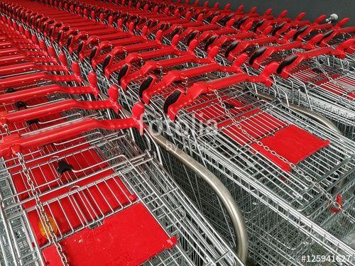 Zusammengeschobene Draht-Einkaufswagen mit Griffen und Kindersitzen aus rotem Kunststoff vor einem neueröffneten Lebensmittelmarkt