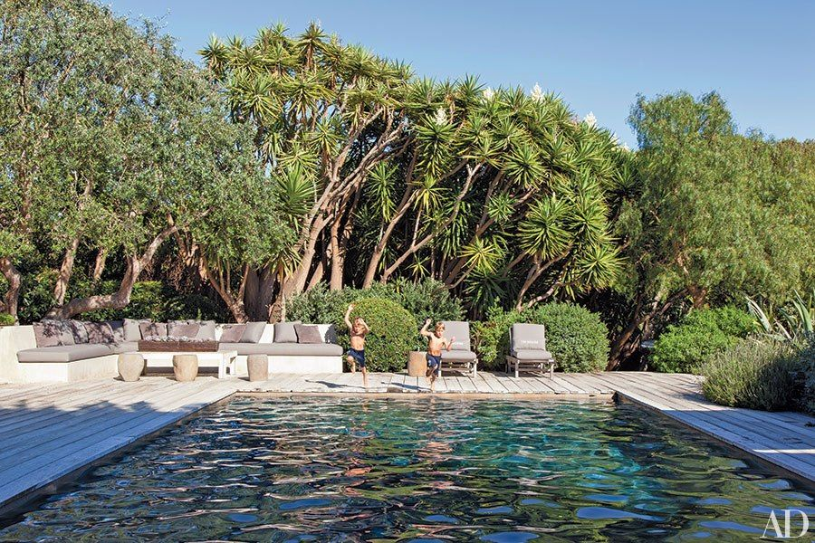 At Jillian and Patrick Dempsey's Malibu home, the family's two sons jump into a swimming pool surrounded by a recycled-wood deck.