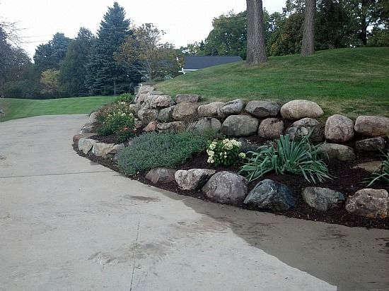 Sloping Driveway Retaining Wall Google Search Landscaping Sloped Garden Landscaping With Rocks Driveway Entrance Landscaping