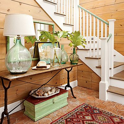 Hand-blown glass lamps and jars in sea glass shades, a nautical map, and a few seashells look collected and personal, not themed. Note the seafoam green stair railing!