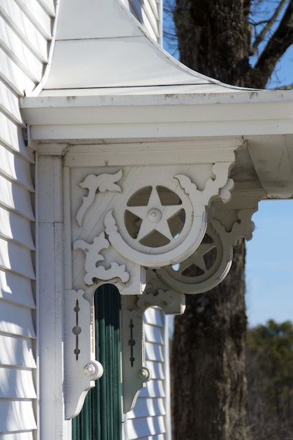 beautiful wood brackets with star detail at the front door overhang