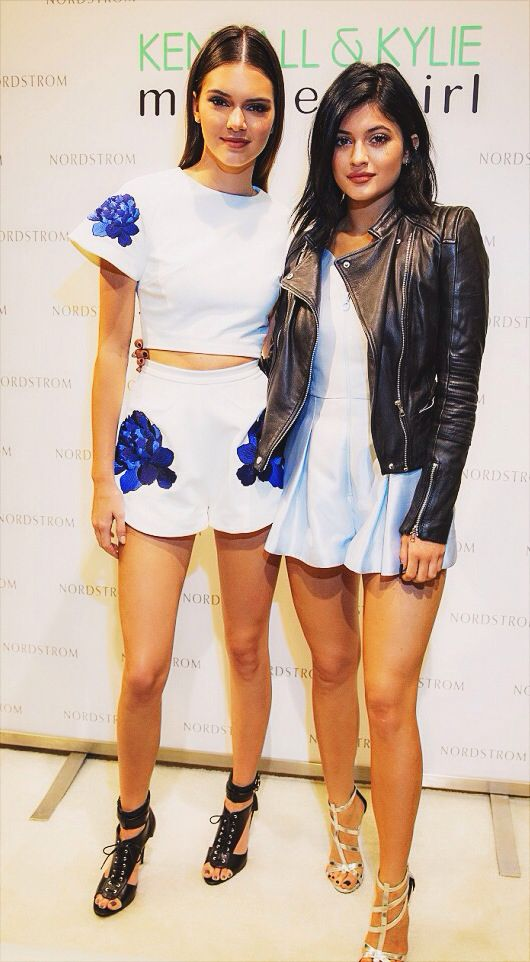 Kylie Jenner wears a powder-blue Alice McCall romper and leather jacket  while posing with Kendall at the Madden Girl meet and greet at Nordstrom in  Seattle.