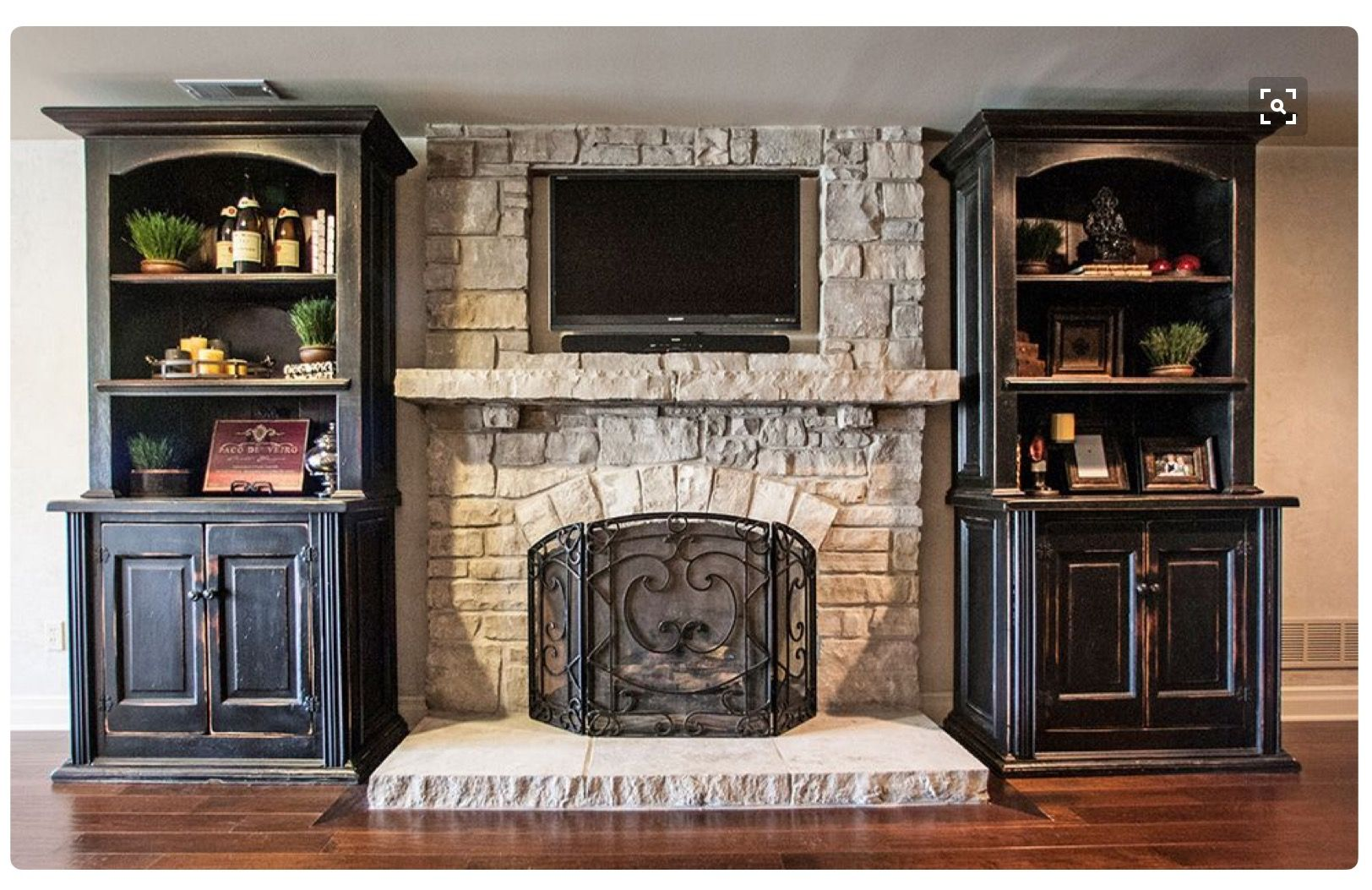Stone Fireplace With Tv And Wooden Shelves On Both Sides