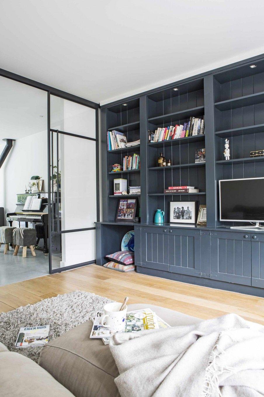 Woonkamer met houten vloer en grote boekenkast | Living room with ...