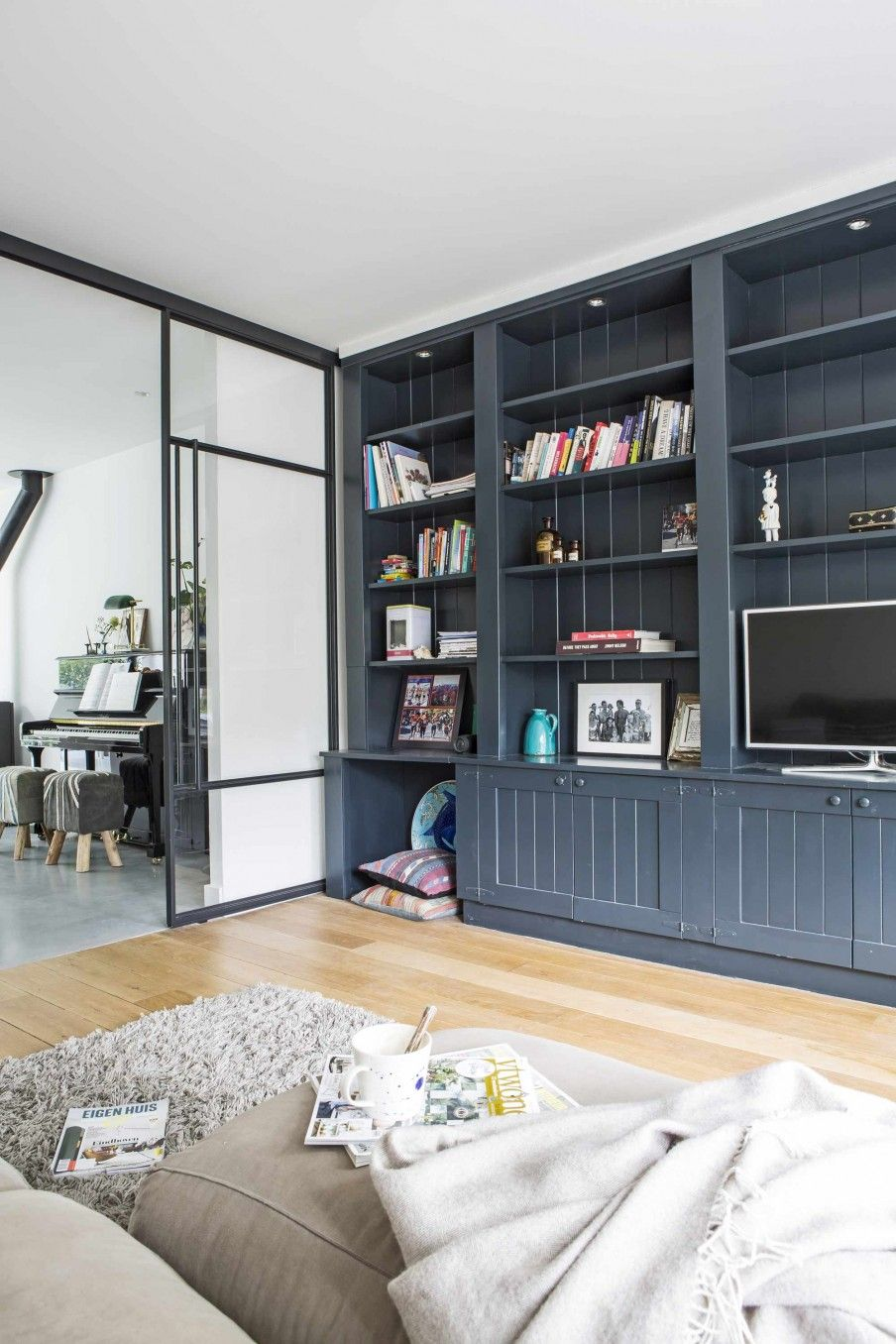 woonkamer met houten vloer en grote boekenkast living room with wooden floor and big bookcase