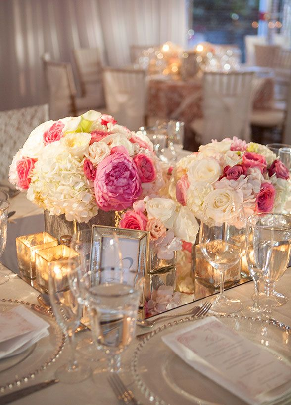 Arrangements of peonies, hydrangeas, and roses in mercury glass vessels sat atop a mirror linen to complete the modern-vintage feel. #WeddingCenterpieces
