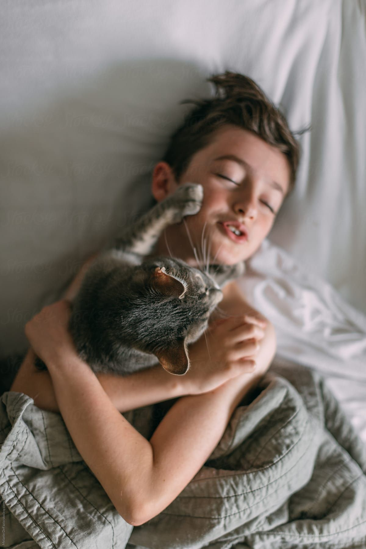A young boy snuggling with his cat in bed on a lazy day