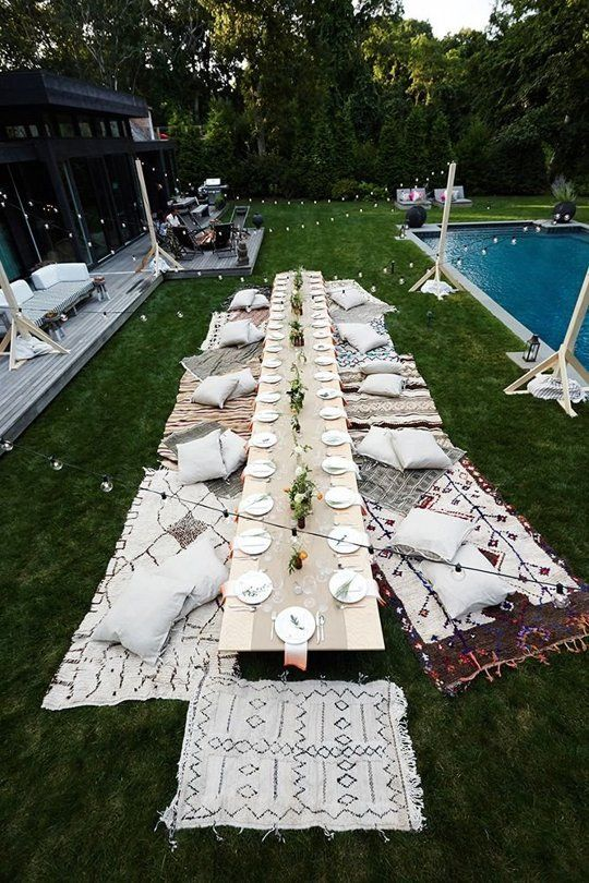 Amazing backyard dinner party setup, with a DIY low table, blankets and pillows on the lawn and strung lights | Eye Swoon