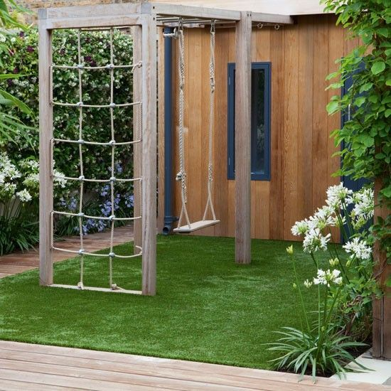 child friendly garden that includes a cedar playhouse swing and climbing frame the ground is covered with maintenance free artificial grass
