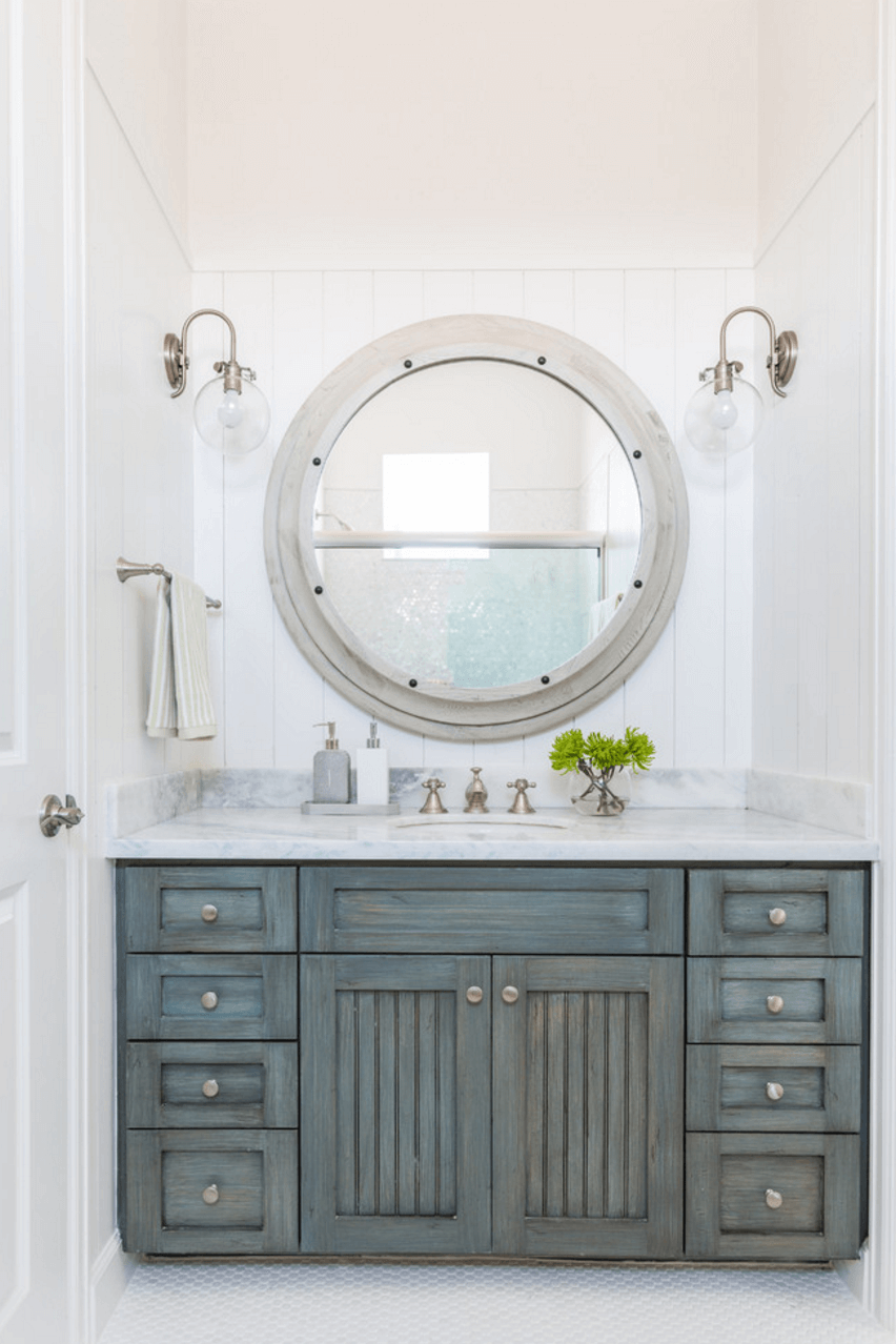Beach House Bathroom This Features Vertical Shiplap Walls Lined With A Large Gray Wood Mirror Illuminated By Clear Gl Barn Sconce Over