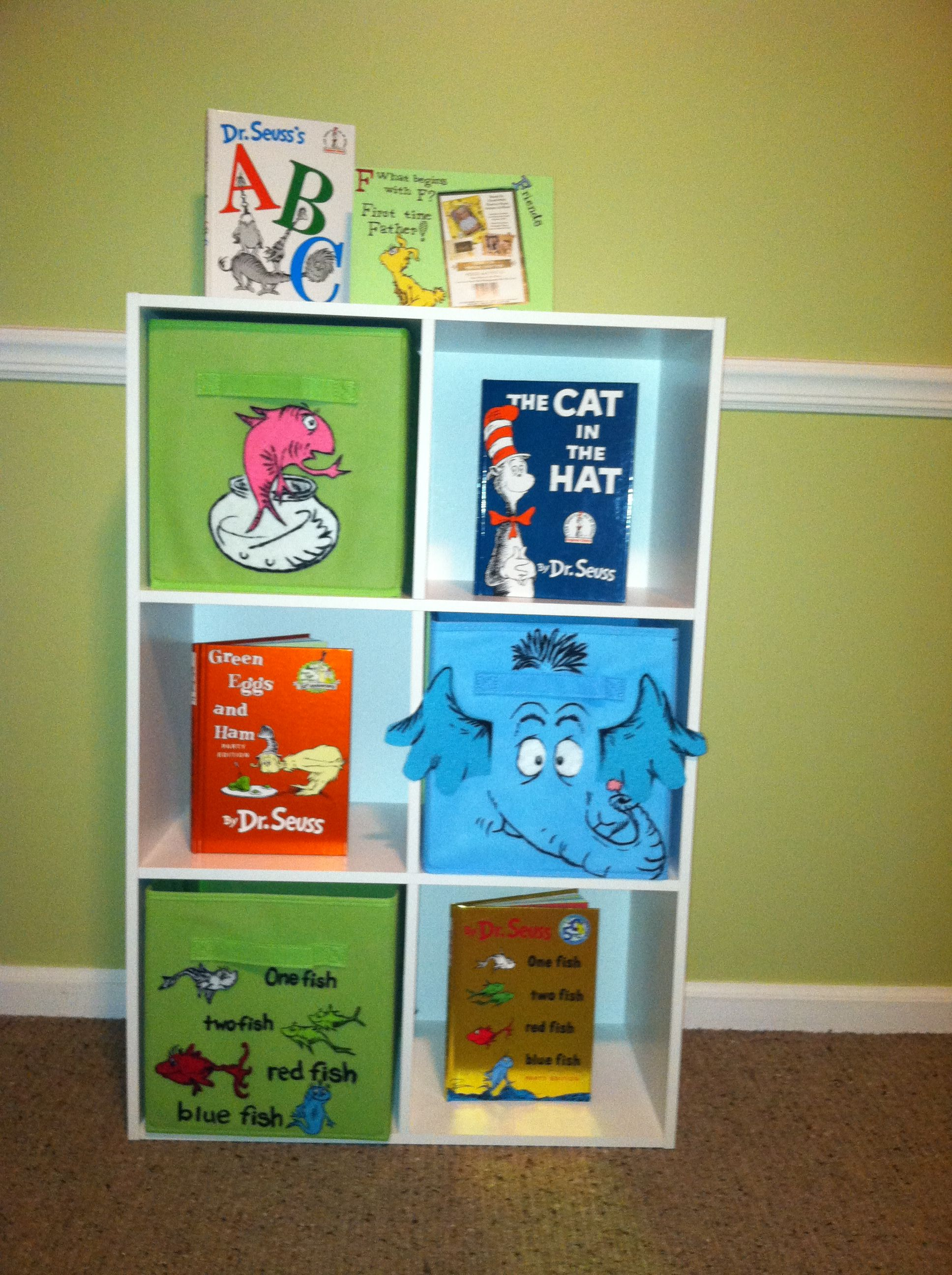 I created this for my nursery. It's just a cubed shelf and three plain cloth bins. They have a variety of colors to choose from. You simply find the characters you would like to incorporate with your nursery theme, then determine the felt colors you'll need. All three crates were customized with felt and black paint for the detailing.