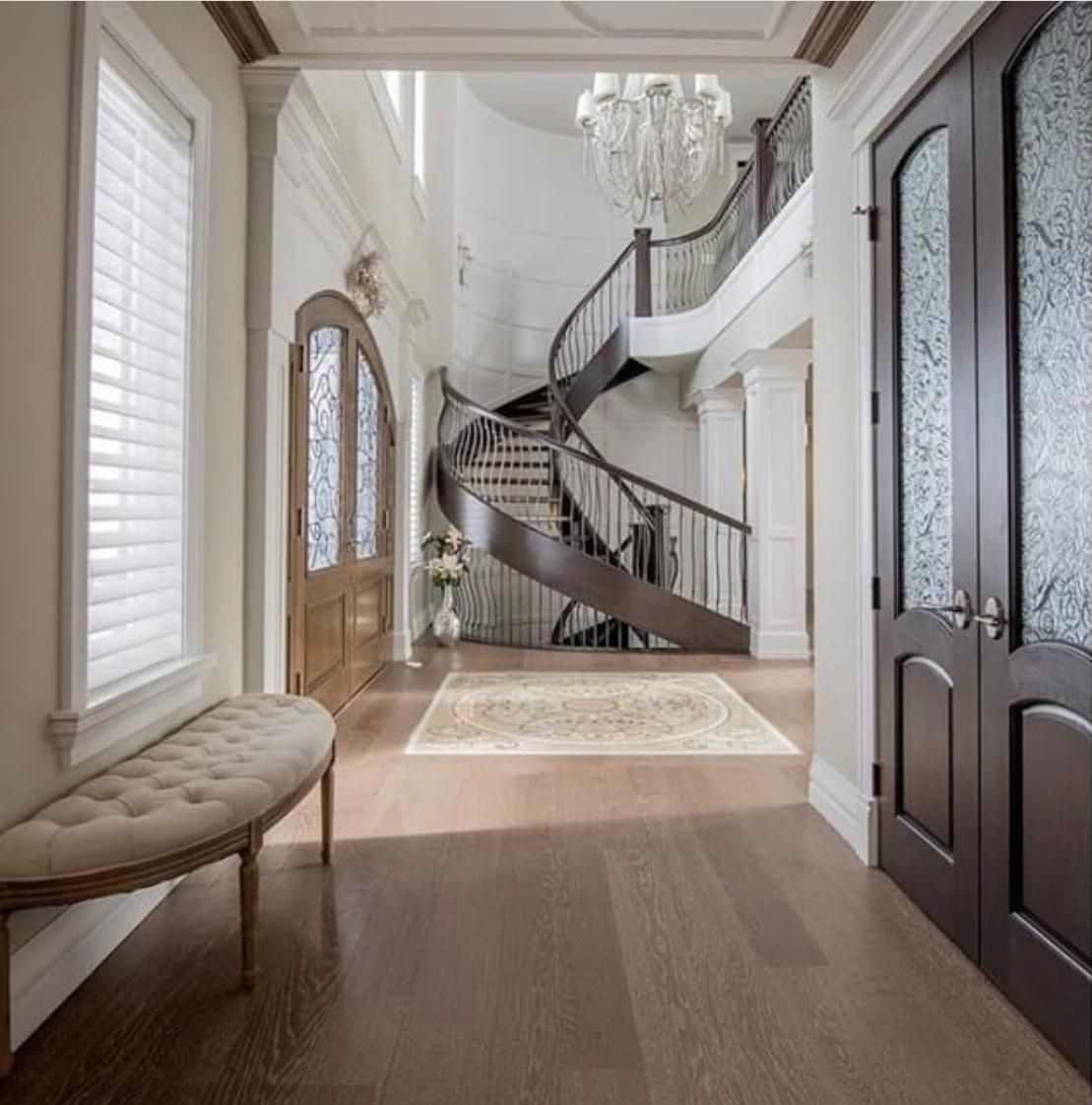 A perfect contemporary entry way. What a maginificient winding staircase! High ceilings, crystal chandelier and hardwood floors. The achictectural trim on the white walls contrasted with dark wood doors is stunning!   SunShine Floor Supplies can help you find the perfect floors for your entry way.   SunShine Floor Supplies, Inc. 147 Selleck Street #6616, Stamford, CT 06902