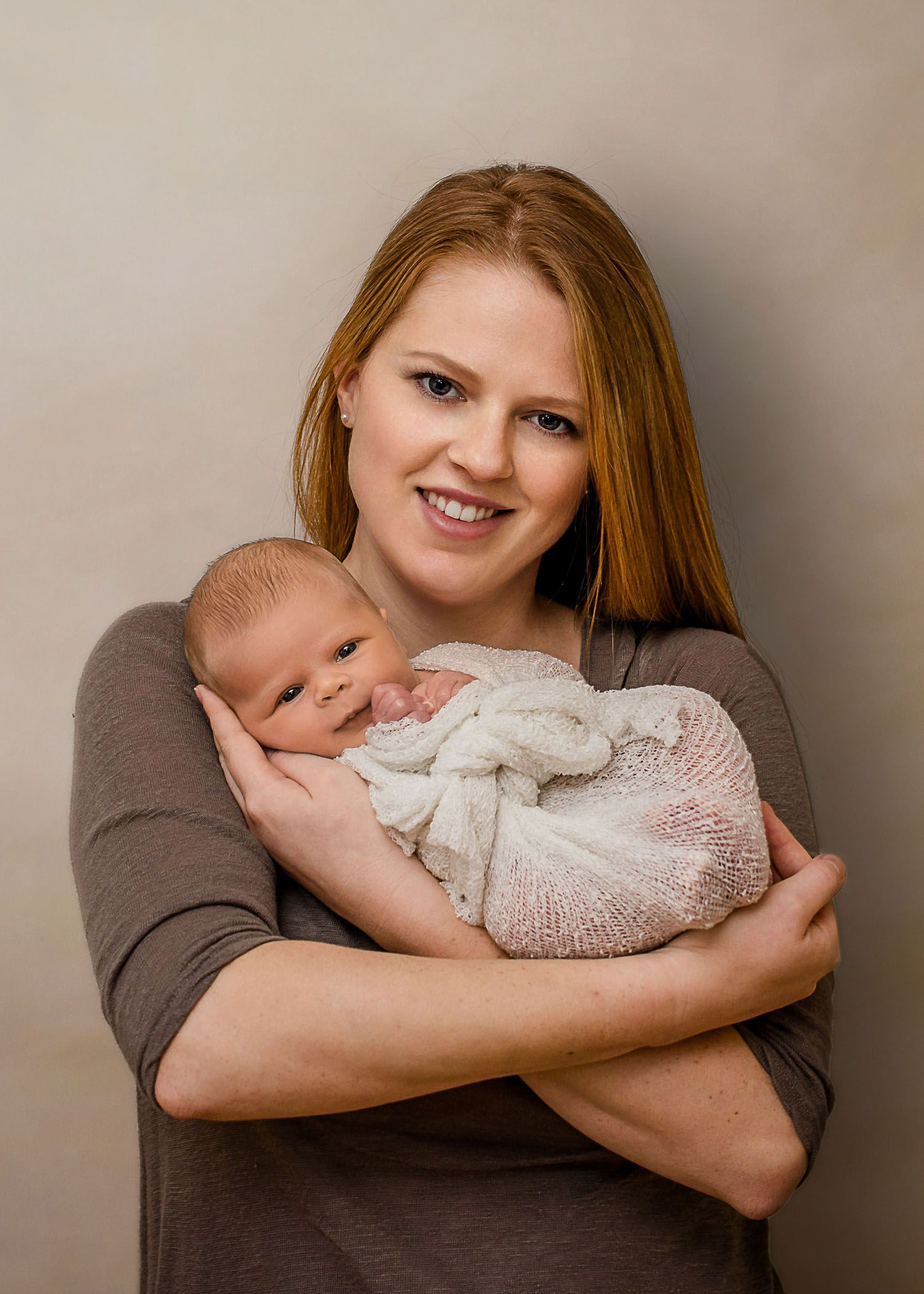 Red haired mom holding baby girl wrapped in her arms