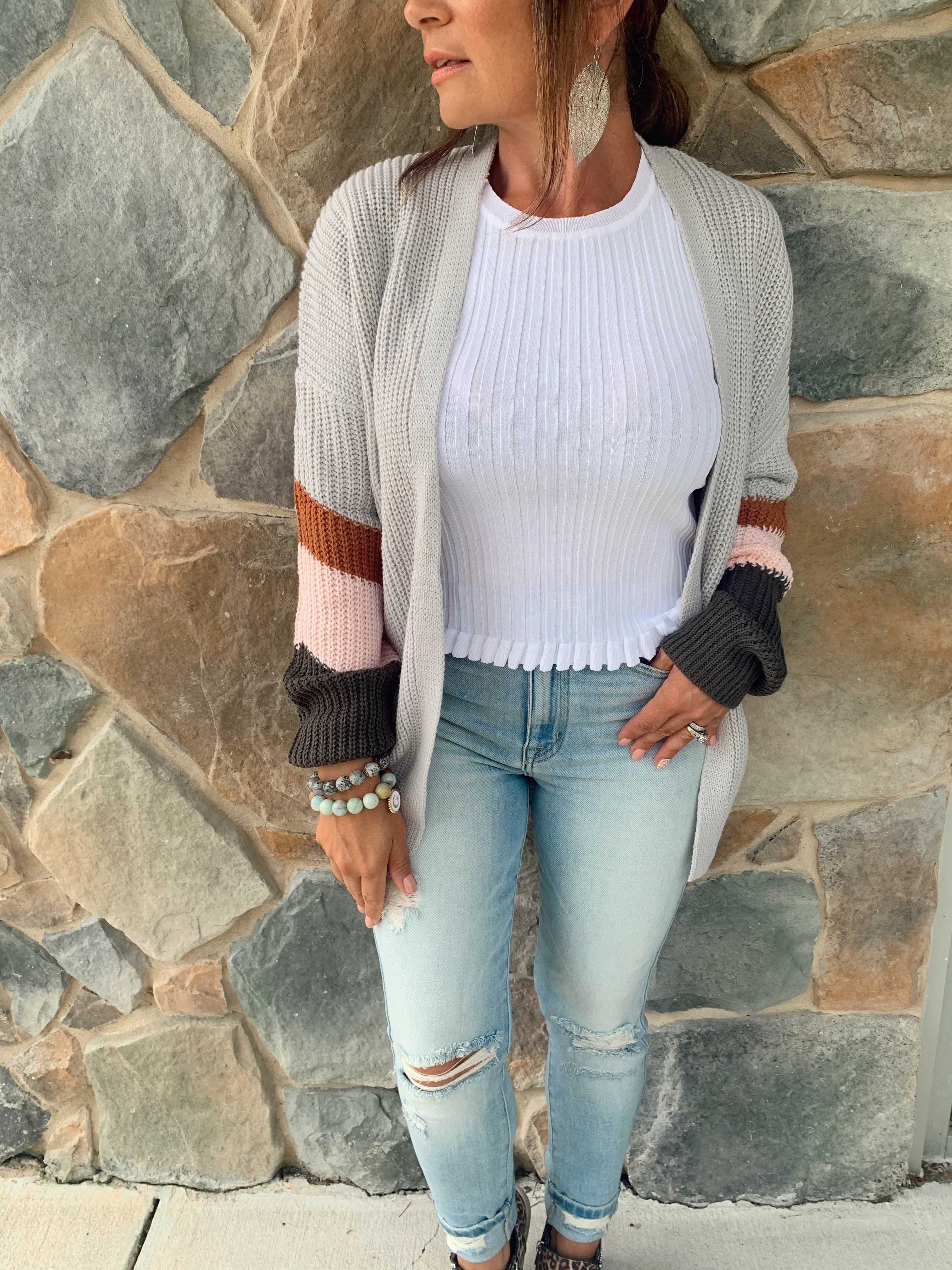 Caren Cardigan What's fall without cardigans? This cozy cardigan is a perfect addition to your closet- the pop of color make it stand out from your typical sweaters. The belt helps give this one piece a few different looks! Size & Fit Our model Gina is 4'11