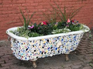 A old claw-foot tub with mosaic tiles and a festive garden planted inside.