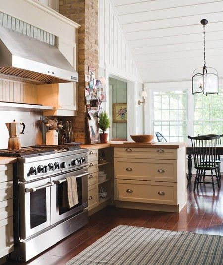 I love the balance in this kitchen! The combination of the stainless steel appliances, white moulded cabinets, brick fireplace, and dark wood floors make this one yummy looking kitchen! Although, I do think I want some granite with the butcher block counters.