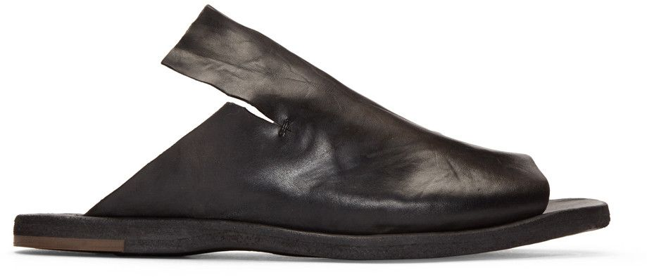 $390 Handcrafted brushed leather slip-on sandals in black. Open round toe. Notch at sides. Tonal leather sole. Tonal stitching.