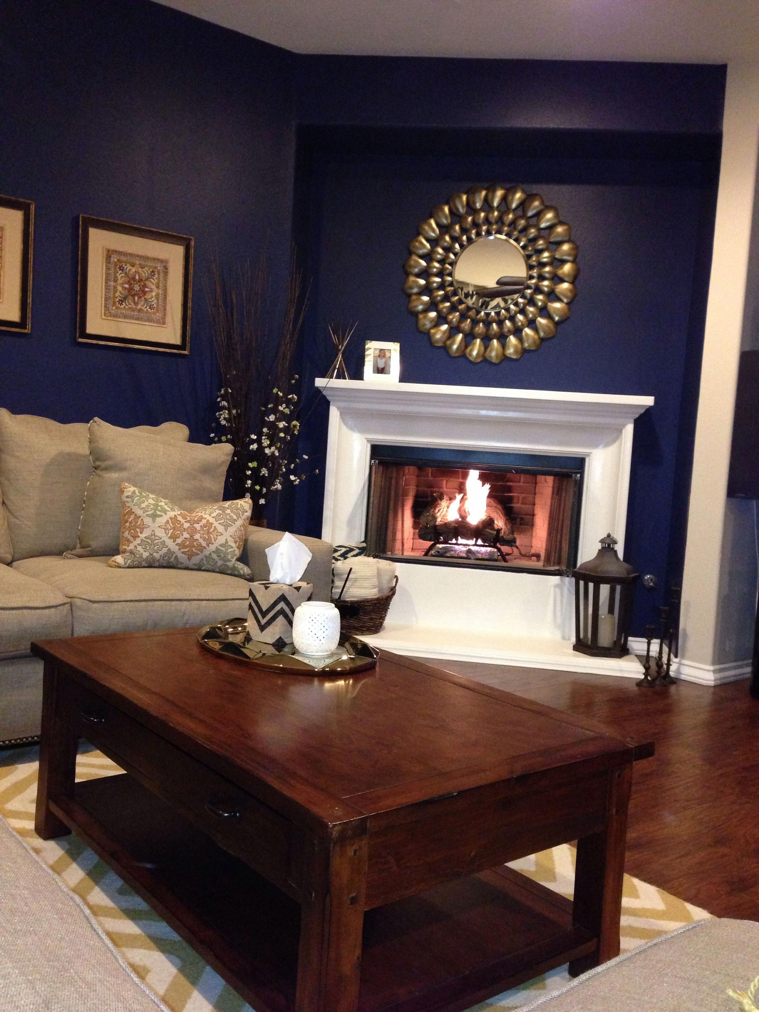 navy blue walls gold accents and a super white fireplace