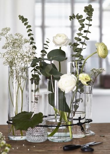 Clear Vases And Glasses Bound Together With Twine Make An