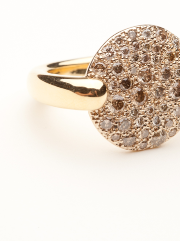 The Sabbia Collection remains one of Pomellato's most exquisite creations. This ring is made of 18kt yellow gold and displays a round disc with a pave of champagne diamonds.
