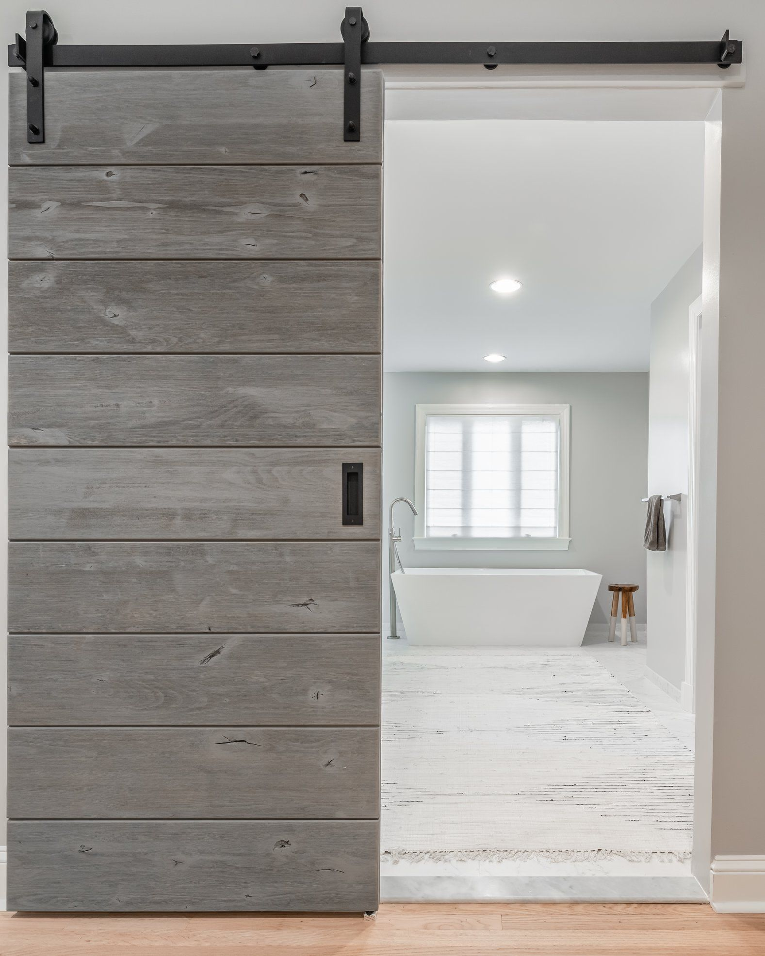 A Rustic Alder Door In A Driftwood Grey Finish On Black Classic Sliding Hardware From Real Carriage Door Sliding Bedroom Doors Rustic Doors Barn Style Doors