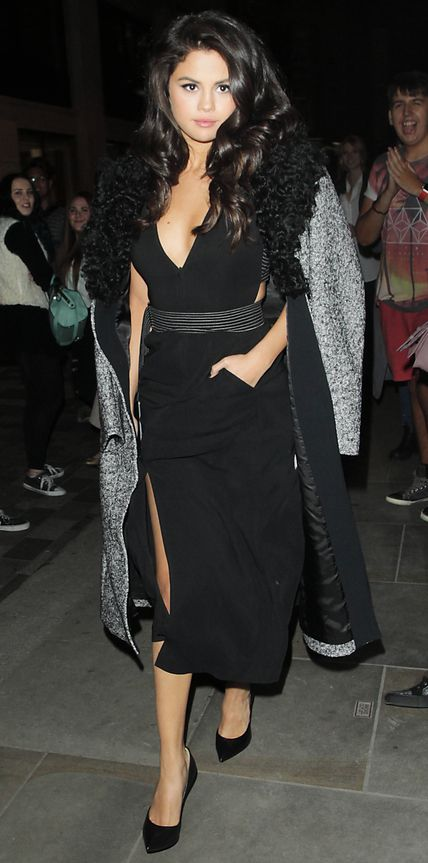 Selena Gomez was a siren in a plunging high-slit belted LBD that she wore with patent black pumps and a gray cocoon coat casually draped over her shoulders.