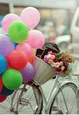 Balloons and a wicker basket full of flowers on a bike