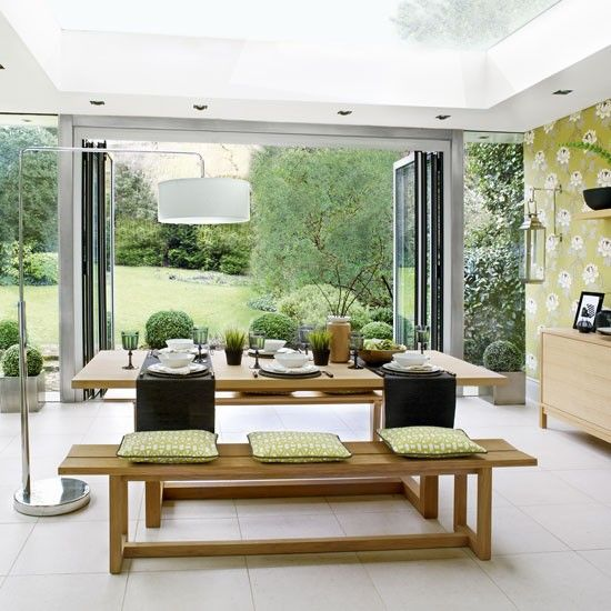 Botanical Dining Room With Bi Folding Doors And Neutral Stone Floor