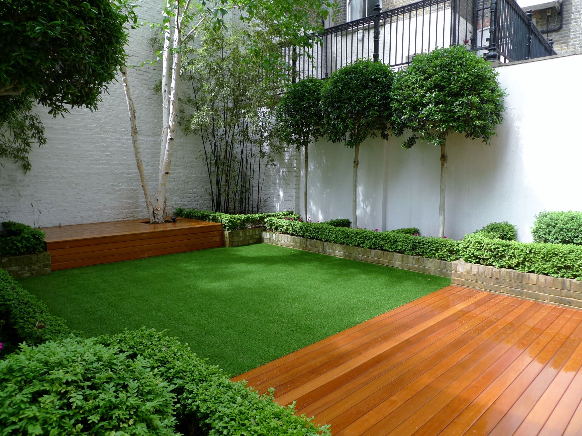 Deck decking london stock brick walls formal topiary low for Garden decking